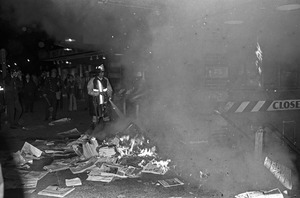 Harvard Square anti-war riot: Burning newspapers at subway kiosk, Cambridge