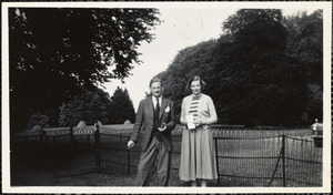 Man and a woman standing in front of a metal fence