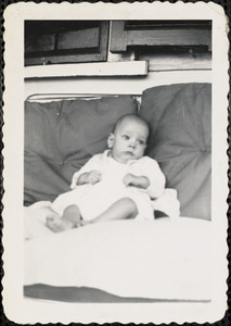 An infant dressed in white sits propped up against two large pillows