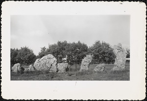 Man standing by a row of pitted standing stones
