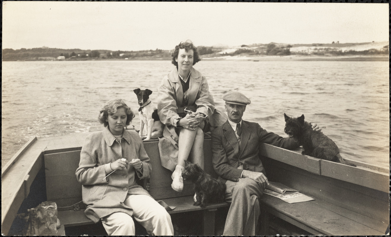 A man and two women sit in a boat with three small dogs