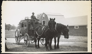 A man in a suit sits high in the driver's seat of a four-wheeled, dark-colored coach drawn by two large black horses