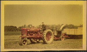 A man sits astride a large, red Farmall tractor