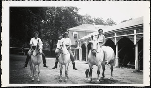 Three women sit astride three light-colored bridled horses, bareback