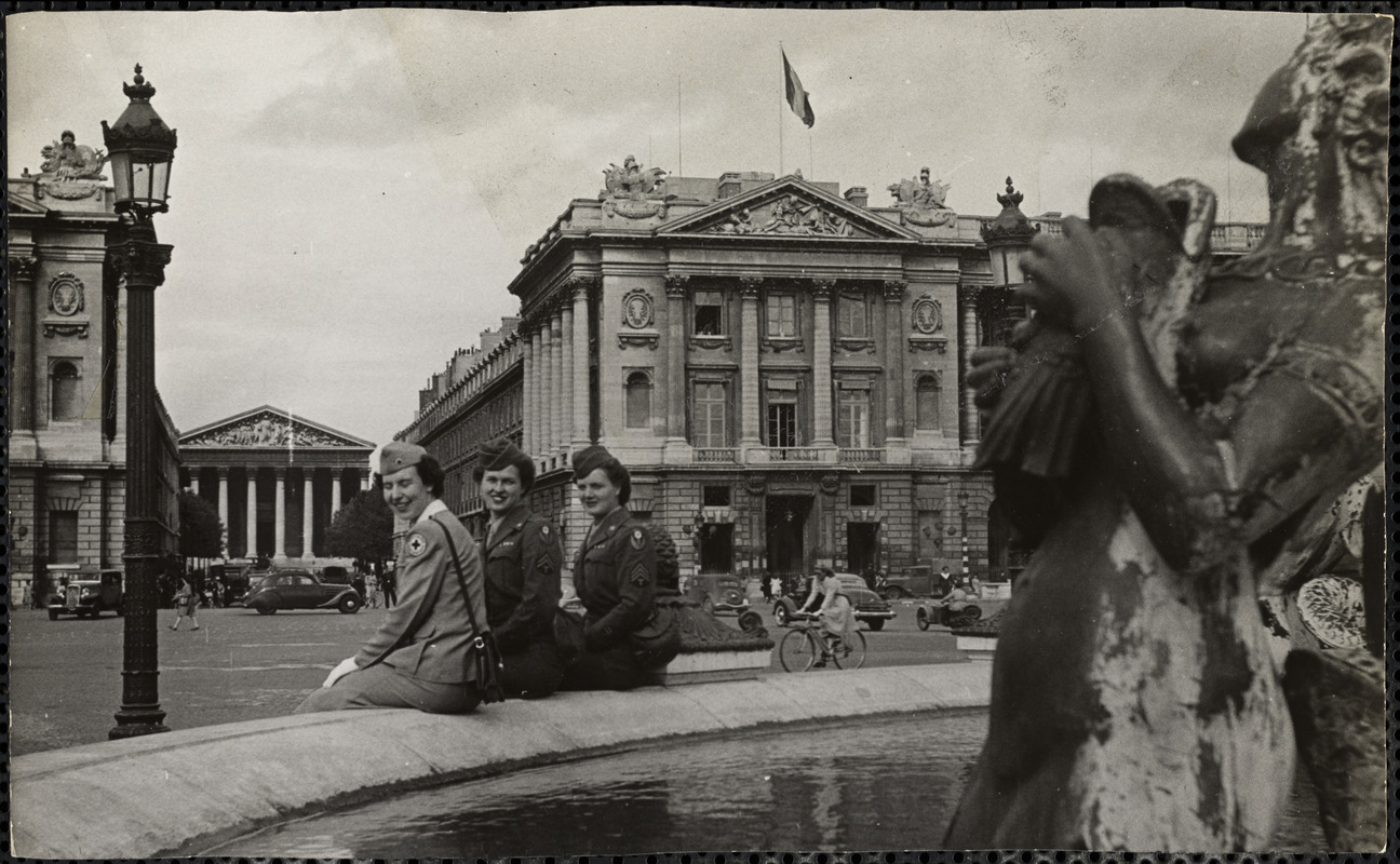 Three women, dressed in military-style uniforms, sit on the edge of a fountain