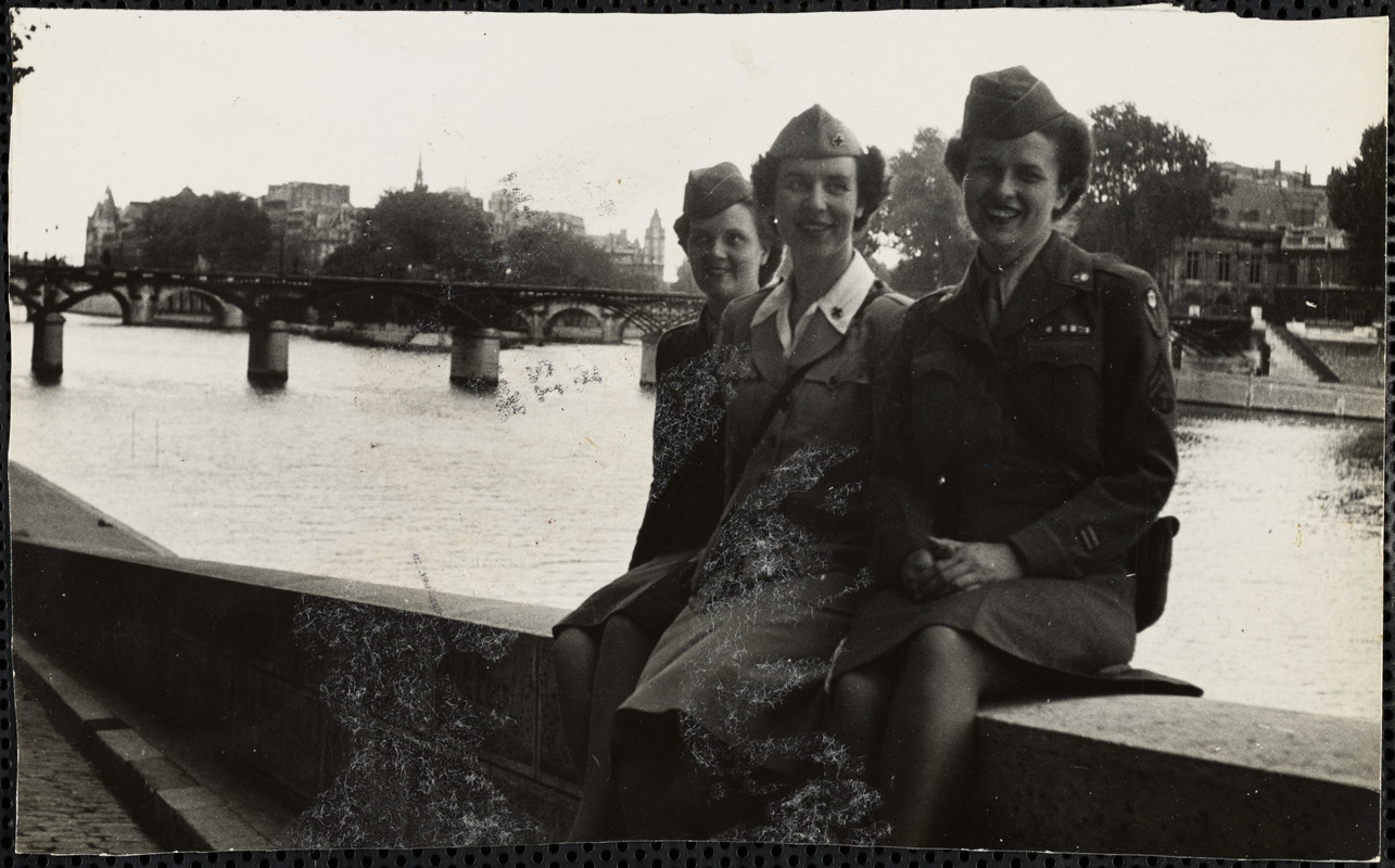 Three women, dressed in military-style uniforms, sit on a stone wall