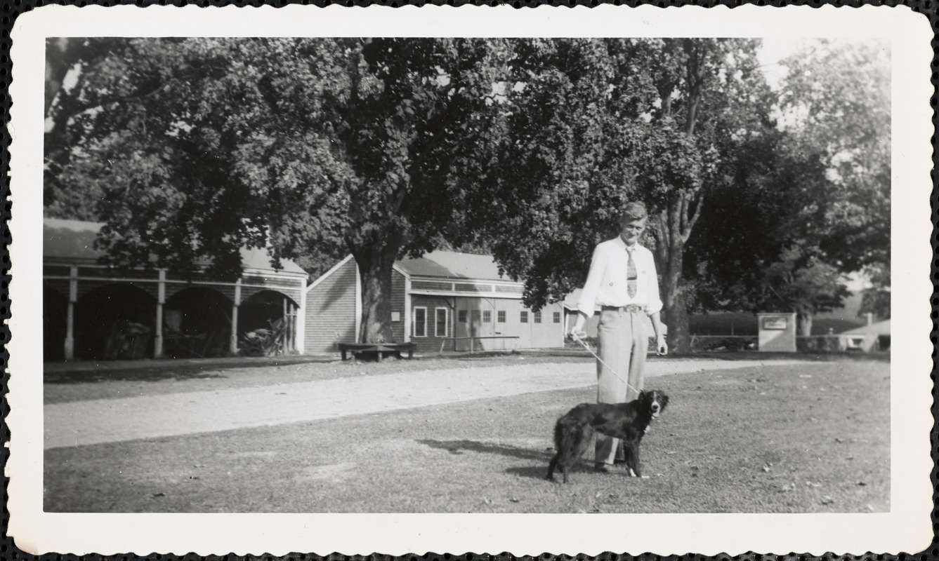 A man holds the leash of a dark-colored dog and stands in an open area