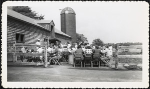 A gathering of men, women, and children sit at, or stand around, tables set up outside a shingled structure, most likely a farm building