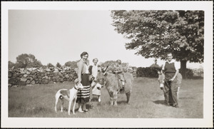 Two women, a young child, a man, gather in front of a stone wall with a greyhound and two donkeys
