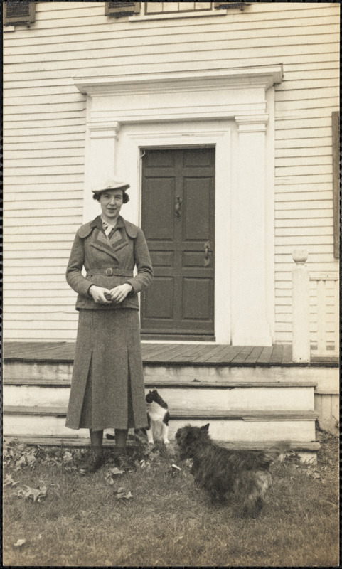 A woman stands in front of a porch with a cat and dog