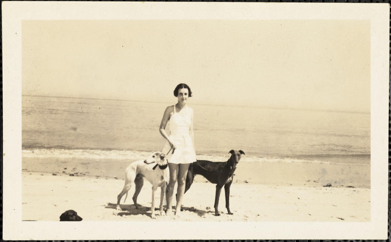 Standing in the sand next to the ocean is a woman holding the leashes of two greyhounds