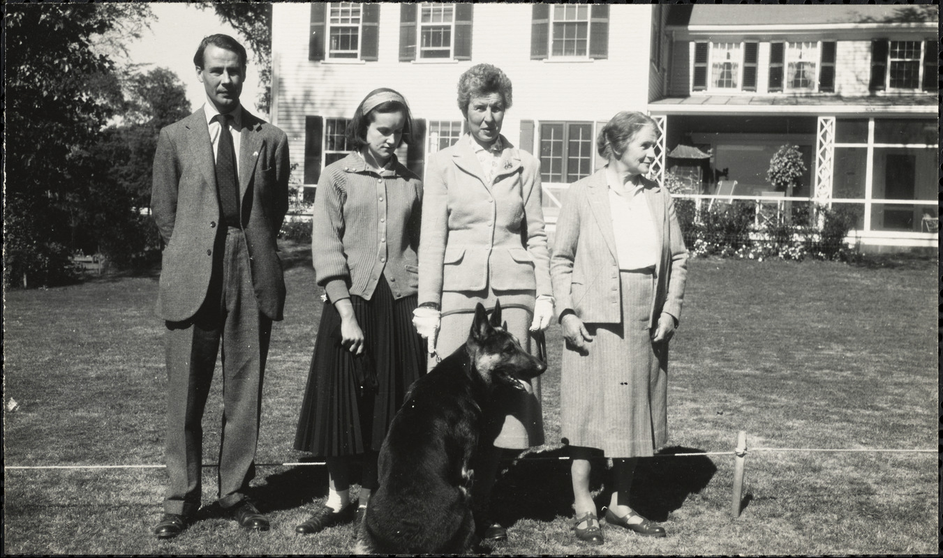 A man and three women stand with a German Shepard on the lawn in front of a light-colored house