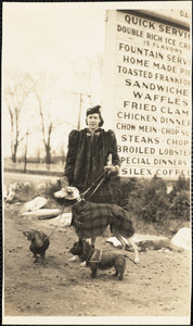 A woman stands in front of a large sign and holds the leashes of three dogs