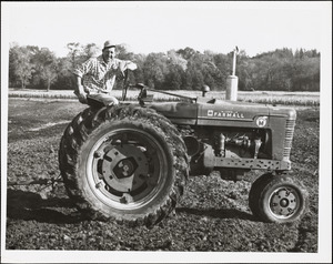 Man sitting on Farmall tractor in plowed field