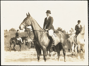 Woman in formal riding clothes astride a horse in a field setting