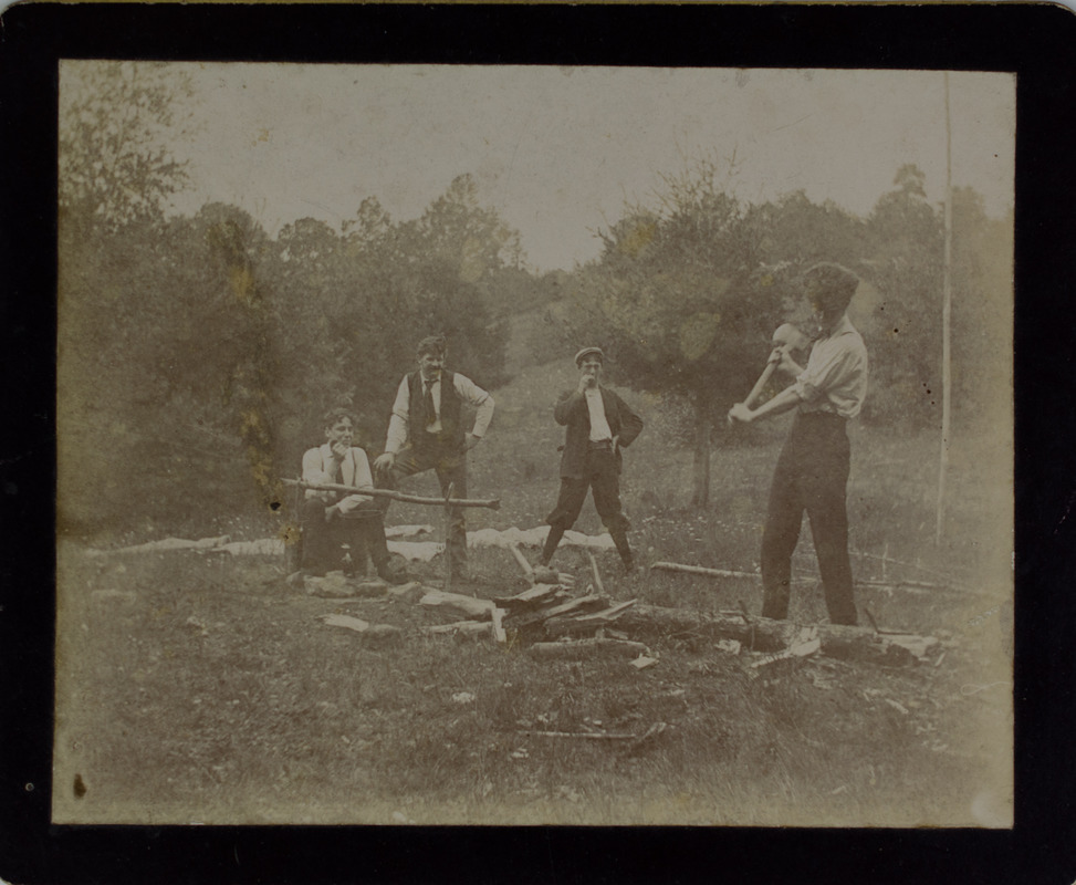 Man chopping wood while friends watch