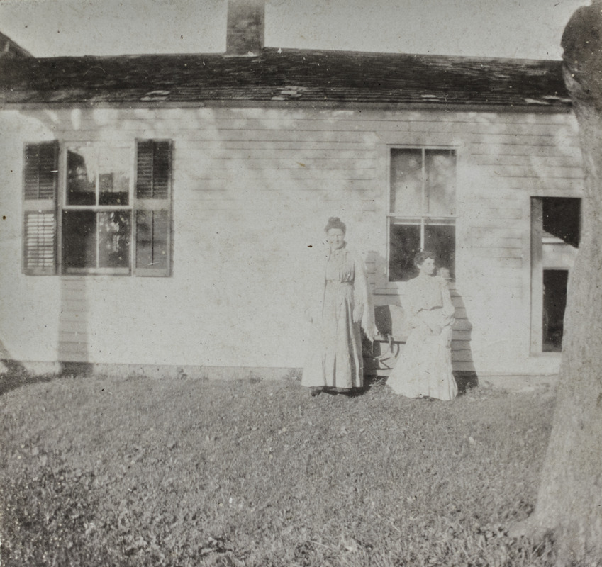 Two unidentified women in front of house wing, 114