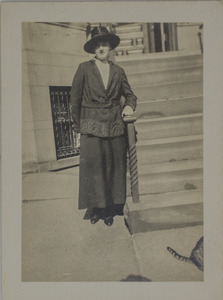 Unidentified woman standing next to steps, 115