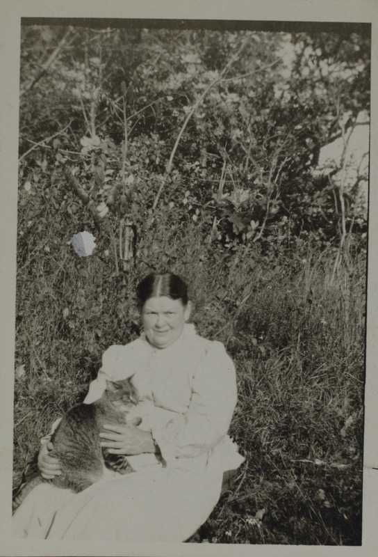 Unidentified woman in garden holding cat, 123
