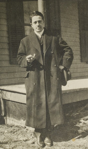 Unidentified young man standing by porch, 122