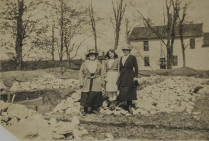 Three women, a house, and some rocks