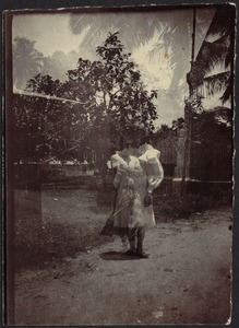 Double exposure of woman in white dress; man with arms crossed; tropical locale