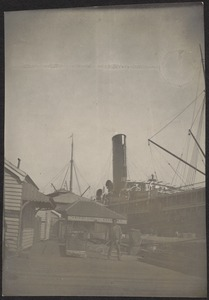 Man standing on dock, steamship behind him at dockside