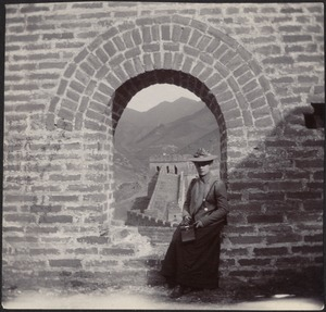 Woman in hat seated in ancient stone arched window, with views of the Great Wall (possibly Laura Conger Buchan or her cousin, Mary Pierce Hammond)