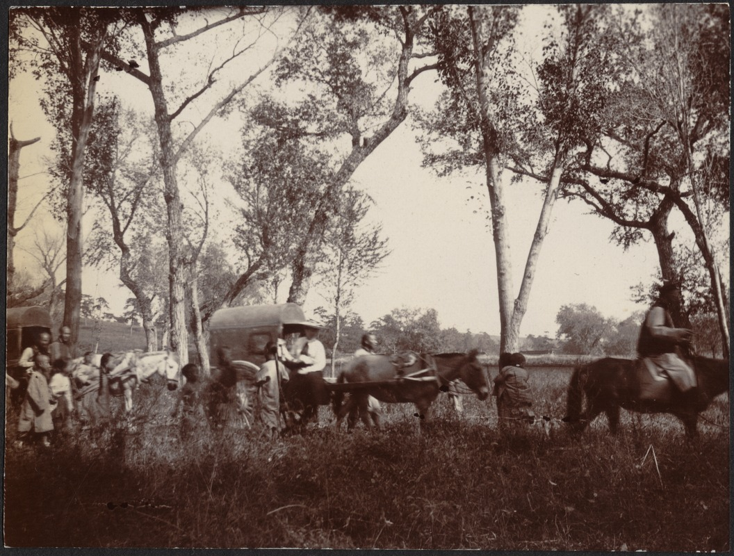 Chinese villagers and one western man in wide-brimmed hat traveling in horse-drawn covered wagons