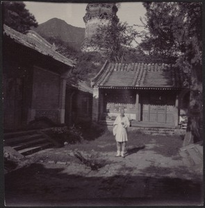 Chinese man in white standing in courtyard; temple tower in distance