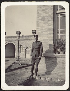 Unidentified man in military uniform standing in front of brick building
