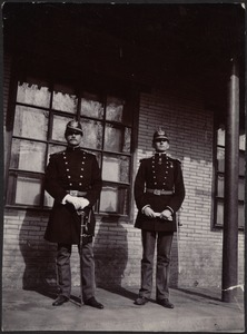 Two unidentified German officers standing in front of brick building