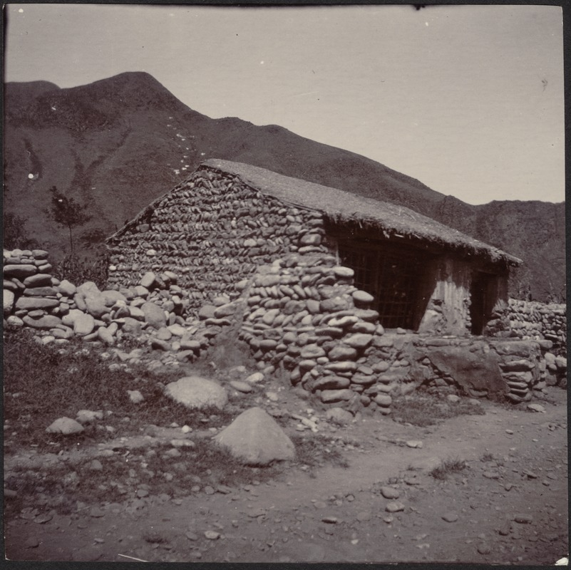 Small stone building with thatched roof in mountains