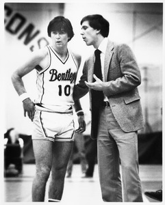 Bentley Falcons basketball coach Brian Hammel consults with player during a game