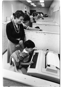 Adult with child at word processing machine