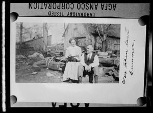 Unidentified man and woman with cat outside a barn