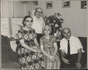 Two women and two men of Changelian family seated in front of flowers