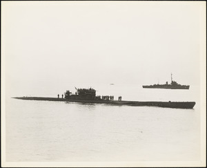 The Third undersea vessel to surrender U-1228 glides into Portsmouth NH early dawn of May 17, 1945 while the DE to which she surrendered [hovers] watchfully in the background