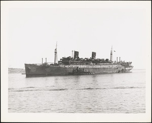 AP-21 USS WAKEFIELD Being towed to US Naval Drydock after fire at sea.  Former Liner SS Manhatten