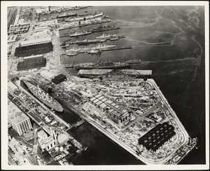 Aerial view of US Naval Dry Dock-BB-61 USS IOWA in dry dock #3-USS BUNKER HILL at East Jetty-AP-21 USS WAKEFIELD at pier