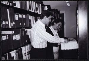 Newton Free Library, Newton, MA. Communications & Programs Office. 2 staff checking reference book in stacks