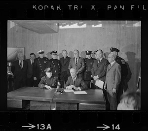 Police Patrolmen's Association President Daniel Sweeney and Mayor Kevin White signing new wage package for Boston Police. In background left to right, two unidentified men, Officer Ray Winston, Deputy Supt. William Bradley, Rev. James Lane, Com. Edmund McNamara, Patrolman Paul Whelan, Superintendent-in-Chief William Taylor, Attorney Robert Wise, and two unidentified men