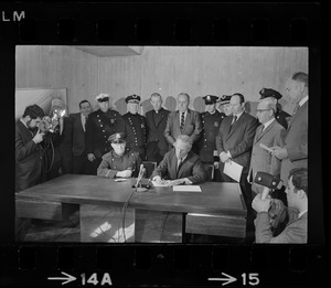 Police Patrolmen's Association President Daniel Sweeney and Mayor Kevin White signing new wage package for Boston Police. In background left to right, two unidentified men, Officer Ray Winston, Deputy Supt. William Bradley, Rev. James Lane, Com. Edmund McNamara, Patrolman Paul Whelan, Superintendent-in-Chief William Taylor, Attorney Robert Wise, and three unidentified men