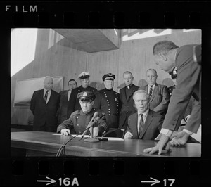 Police Patrolmen's Association President Daniel Sweeney and Mayor Kevin White signing new wage package for Boston Police. In background left to right, Two unidentified men, Officer Ray Winston, Deputy Supt. William Bradley, Rev. James Lane, Com. Edmund McNamara, and Patrolman Paul Whelan
