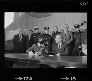 Police Patrolmen's Association president Daniel Sweeney signs new wage package for Boston Police yesterday as Mayor White (right) and police officials watch