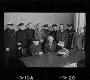 Police Patrolmen's Association President Daniel Sweeney and Mayor Kevin White signing new wage package for Boston Police. In background left to right, Officer Ray Winston, Deputy Supt. William Bradley, Rev. James Lane, Com. Edmund McNamara, Patrolman Paul Whelan, Superintendent-in-Chief William Taylor, Attorney Robert Wise, and three unidentified men