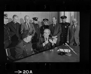 Police Patrolmen's Association President Daniel Sweeney and Mayor Kevin White signing new wage package for Boston Police. In background left to right, Deputy Supt. William Bradley, Rev. James Lane, Com. Edmund McNamara, Patrolman Paul Whelan, Superintendent-in-Chief William Taylor, Attorney Robert Wise, and two unidentified men