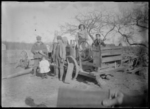 People with small kid in foreground on hitched wagon - machine with wheel - to clean cranberries