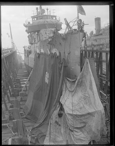 Sheeting being hung around Coast Guard ship USS Paulding at Navy Yard to protect workmen from wind and cold while they repair bow damaged when she rammed and sank the S-4.