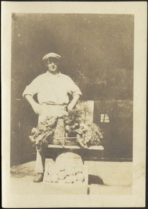 Unidentified gardener standing behind small table with a bounty of vegetables